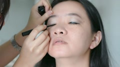 Woman is doing facial cosmetic makeup using eyeliner pencil to a model in HD Stock Footage