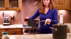 A woman moving a hot pot over to a counter with pot holders Stock Footage