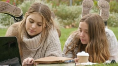 Two young woman students working together in park studying on laptop computer Stock Footage