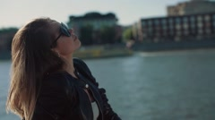girl in the wind sits on the waterfront in slowmotion - stock footage