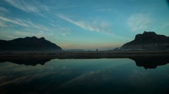 Wide shot across still lagoon water reflecting mountain and clouds.Time lapse Stock Footage