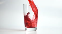 Pouring red cherry juice into glass Stock Footage