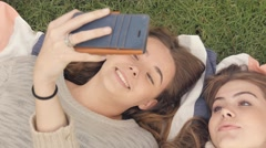 Girlfriends having a good time together laughing being silly taking selfie Stock Footage