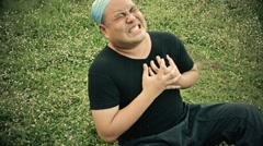 Fat Asian man having a heart attack and die on grassy ground field in film grain Stock Footage