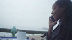 4k Young woman talking on mobile phone and drinking coffee at seafront cafe Stock Footage