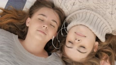 Bff best friends sharing headphones listening to music relaxing outdoors Stock Footage