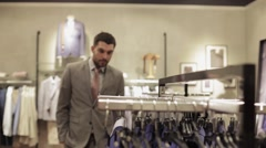 Young man choosing clothes in clothing store Stock Footage