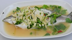 Person eating spicy steamed seabass lemon soup in restaurant as Thai cuisine Stock Footage