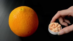 An orange fruit is compared to the bowl of vitamin c supplements - stock footage