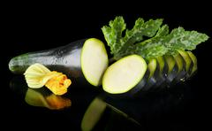 Mature dewed zucchini cut into slices with flower and courgette leaf on black Stock Photos