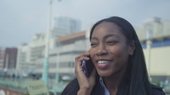 4K Portrait of young woman talking on mobile phone in coastal town Stock Footage