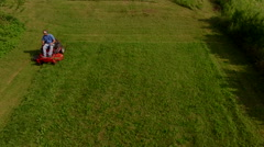 Tracking elevaated view of man on a riding lawn mower Stock Footage