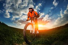 wide angle portrait against blue sky of mountain biker Cyclist - stock photo
