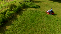 Tracking elevated view  of man on a riding lawn mower Stock Footage