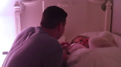 A father tucks his daughter into bed and gives her a goodnight kiss Stock Footage