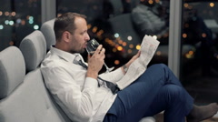 Young businessman reading newspaper and drinking wine on sofa during night - stock footage