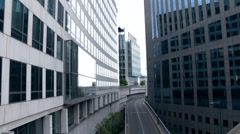 Two cars drive along overhead road in deserted district - stock footage
