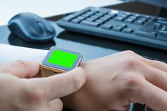 Business man using smartwatch app with chroma key green screen near keyboard  Stock Photos