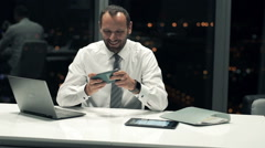 Young businessman playing game sitting by desk in the office during night Stock Footage