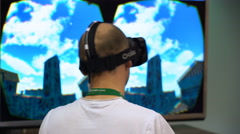 Virtual reality game. A young man uses head mounted display Oculus Rift. Stock Footage