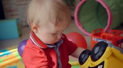 Little boy playing with toy car lying on the floor Stock Footage