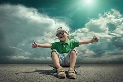 Child with skateboard under sunlight. - stock photo