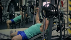 Handsome athletic man doing pectorals with bench press trainer with dumbbells on Stock Footage