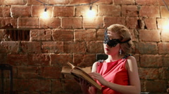 Glamorous blonde woman in a red dress reads a book. Fashion 18th century. RAW Stock Footage