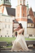 Girl in luxurious long dress on street of old town Stock Photos