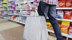 KIEV, UKRAINE - FEBRUARY 22, 2016: A man walking in with bags supermarkete Stock Footage