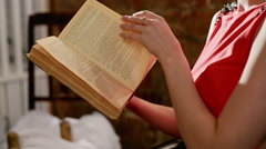 Beautiful mysterious girl reading a book. Close up. RAW video record Stock Footage
