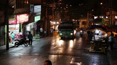 Large green bus slowing climbing up a street at night in the city of Medellin, Stock Footage