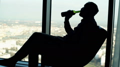 Silhouette of drunk man drinking wine on armchair by the window Stock Footage