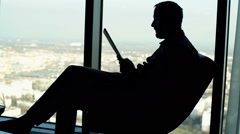 Silhouette of man reading magazine sitting on chair at home by the window Stock Footage