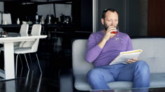 Young man reading newspaper and drinking red wine sitting on sofa at home Stock Footage