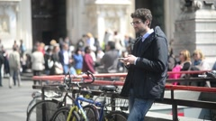 Young Man brunette with mobile phone in hand - chating sms near Duomo in Milan Stock Footage