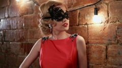 Beautiful blonde girl in gorgeous red dress with a mask on her face in a vintage Stock Footage