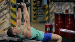 Handsome athletic man doing pectorals with breeding hands with dumbbells on benc Stock Footage