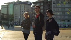 Group of three tourists looking around the city square slow motion Stock Footage