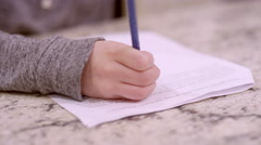 A young boy working on homework at the kitchen counter Stock Footage