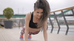 Beautiful black haired, curly fitness model, stretching and exercising outdoor - stock footage