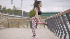 Beautiful, black haired girl exercising with pink dumbbells outdoors Stock Footage
