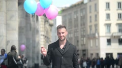 Nice guy smiling with colorful balls - the center of Milan Italy Stock Footage