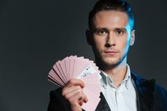 Serious young man magician holding playing cards with ace Stock Photos