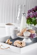 Sweet cookies on white tray with bottles of milk and lilak flowers Stock Photos