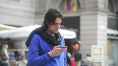 Young Man brunette with mobile phone in hand - chatting sms, center street Milan Stock Footage
