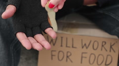 Poor man begging for change, holding coins in his hands, will work for food sign Stock Footage