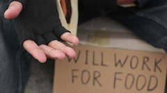 Man begging for change with outstretched hand, homeless sitting in the street Stock Footage