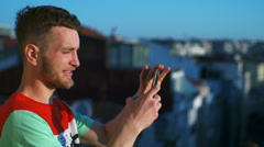 young man taking picture of a city from a balcony using smartphone slow motion - stock footage