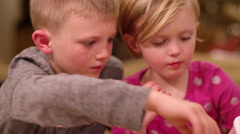 Siblings scooping ice cream at home, close up, little girl licks the spoon Stock Footage